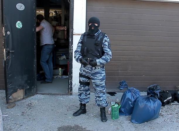 В мешках у ног собровца - около 15 кг различных наркотиков. Фото: 39mvd.ru.