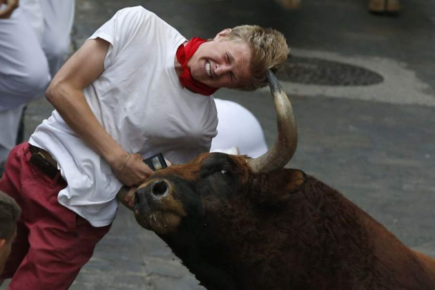 Бык поднимает человека на рога.