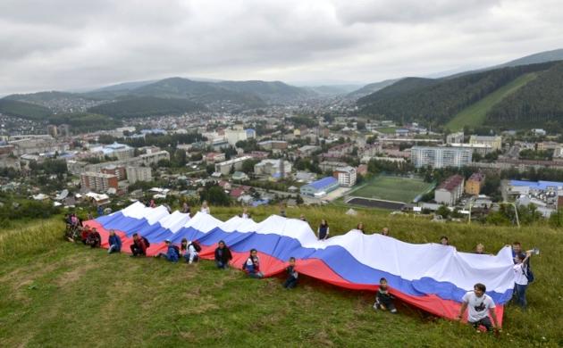 На одной из горно-алтайских вершин развернули 40-метровый российский флаг. Фото: пресс-служба регионального отделения «Единой России»