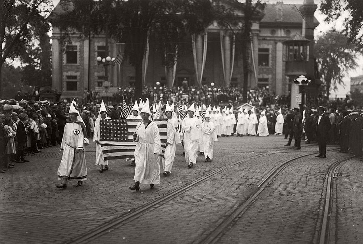 Женщины из Ку-клукс-клана маршируют держа американский флаг по Бингхэмтону, Нью-Йорк. 1920-е
