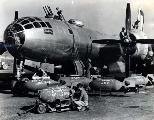 Техники загружают боеприпасы на бомбардировщик B-29 перед вылетом на бомбардировку Токио