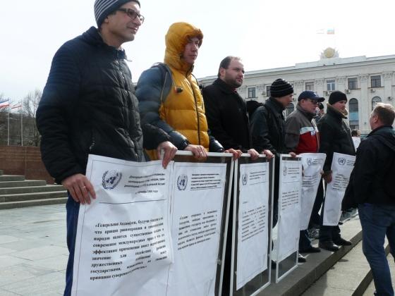 Митингующие с Уставом ООН на митинге в поддержку референдума в Симферополе. Март 2014