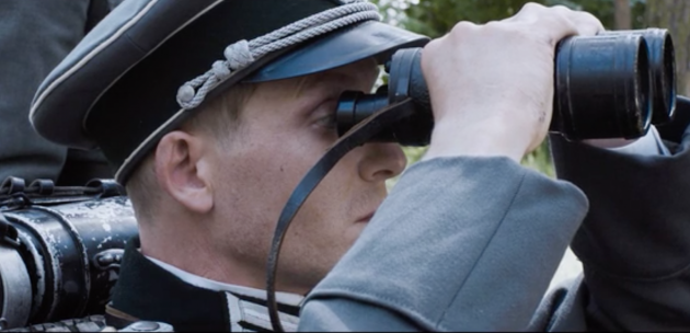 Ханс уже в офицерской форме, смотрит в бинокль сквозь созданные им же линзы
