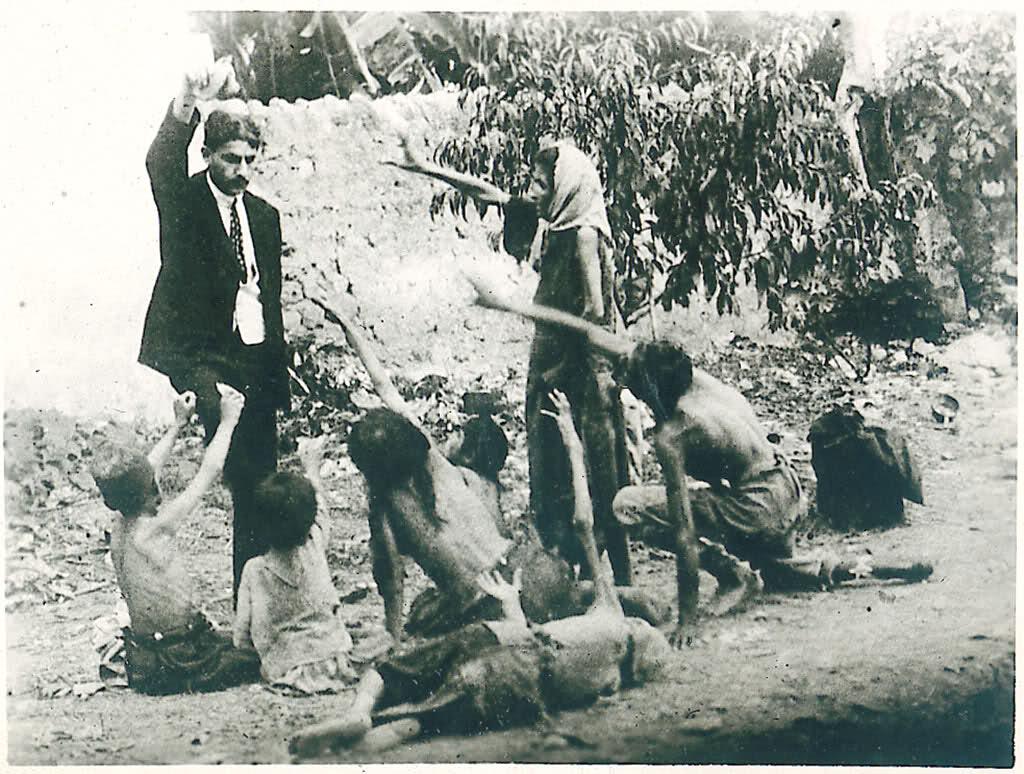 Турок дразнит голодающих армянских детей хлебом. 1915