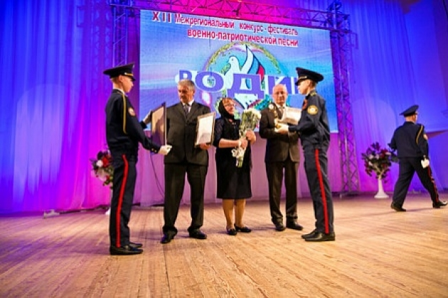 Родителям Александра Прохоренко вручают документ, согласно которому патриотический фестиваль носит имя их сына-героя