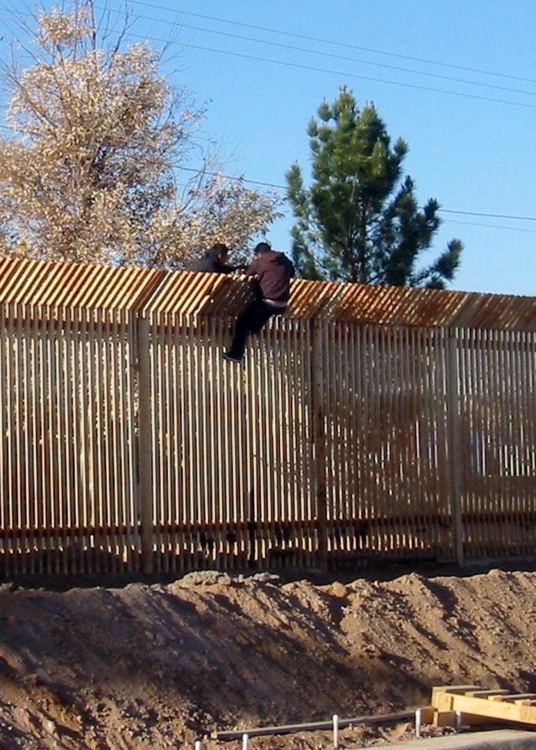 Нелегальные иммигранты перелезают через забор на американо-мексиканской границе