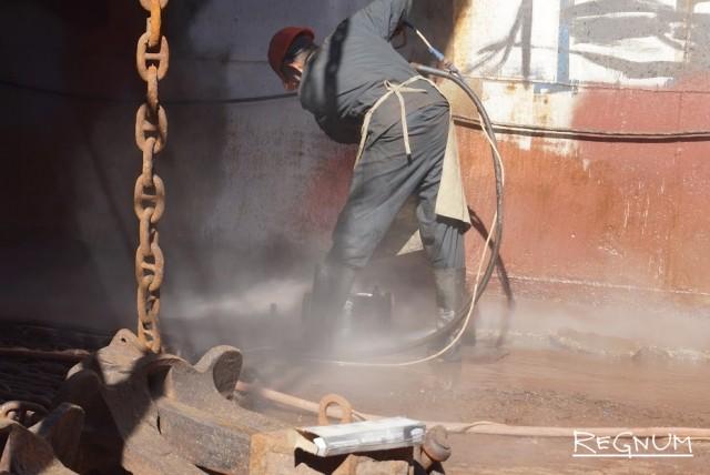 Потоком воды под высоким давлением корпус корабля очищают от ракушки и старой краски