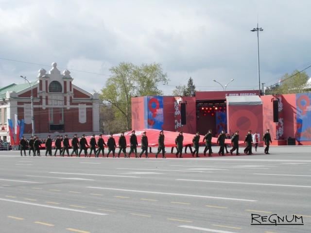 В завершение парада войск на площадь Ленина в Новосибирске вынесли точную копию знамени Победы размером 10 на 20 метров