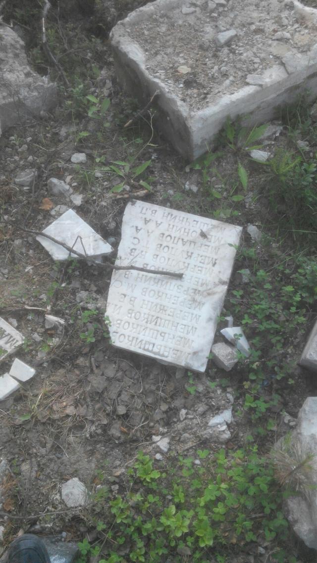 Плиты с именами похороненных бойцов разбросаны на братском кладбище Карелии (п. Сосновый). Июль 2017 года