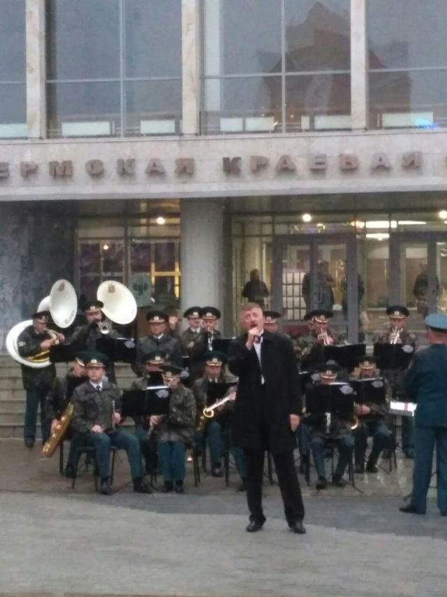 Концерт под дождём. Десятки человек слушают живую музыку возле здания Законодательного собрания Пермского края и краевой избирательной комиссии