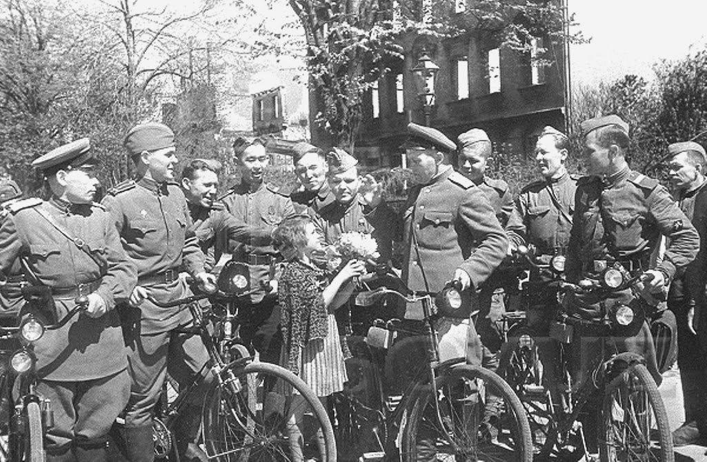 Немецкая девочка дарит цветы советским военным. Кёнигсберг, июнь 1945 года