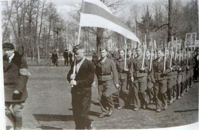 С бело-красно-белым флагом и плакатами Гитлера полицаи, из числа белорусских националистов и коллаборационистов и все вместе на службе немецкому сапогу. На переднем плане, в центре – Борис Рагуля, командир 68-го карательного белорусского батальона. Батальон сжёг около 20 деревень