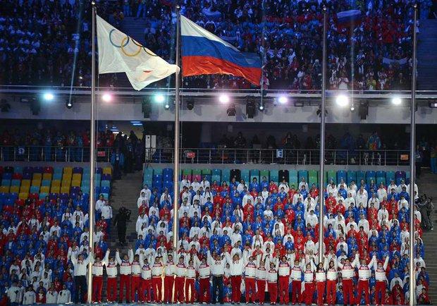 Олимпийский и российский флаги на церемонии закрытия Олимпийских игр 2014