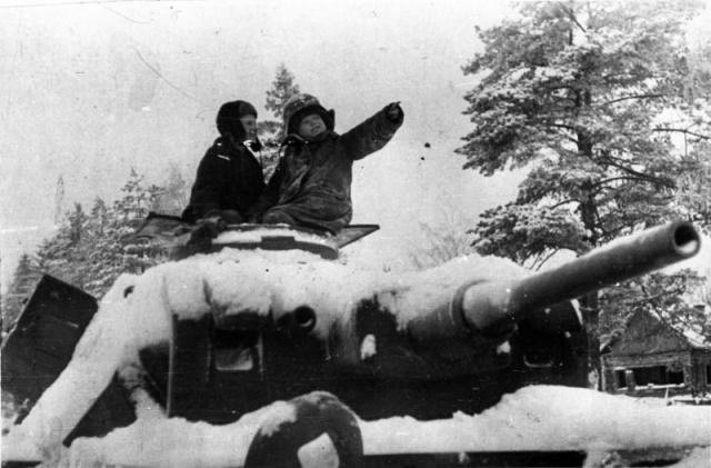 Деревенские дети сидят на башне подбитого и брошенного немецкого танка Pz.Kpfw.III. Зима 1941 -1942 гг