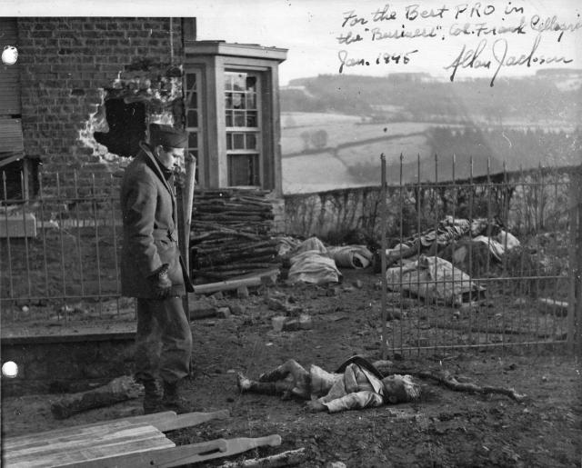 Американский солдат у тела убитого немцами бельгийского мальчика. На заднем плане — тела других расстрелянных. Ставело, Бельгия, 1944 г