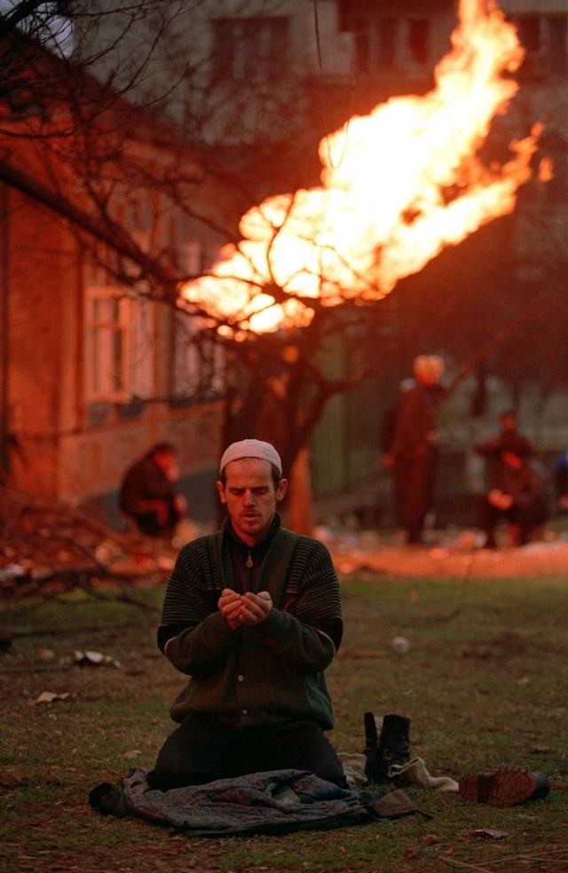 Чеченец молится в Грозном, январь 1995 г. На заднем фоне горит перебитая осколками газовая труба.