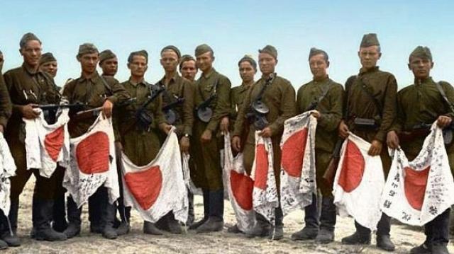 Советские солдаты с трофейными японскими знамёнами. 1945