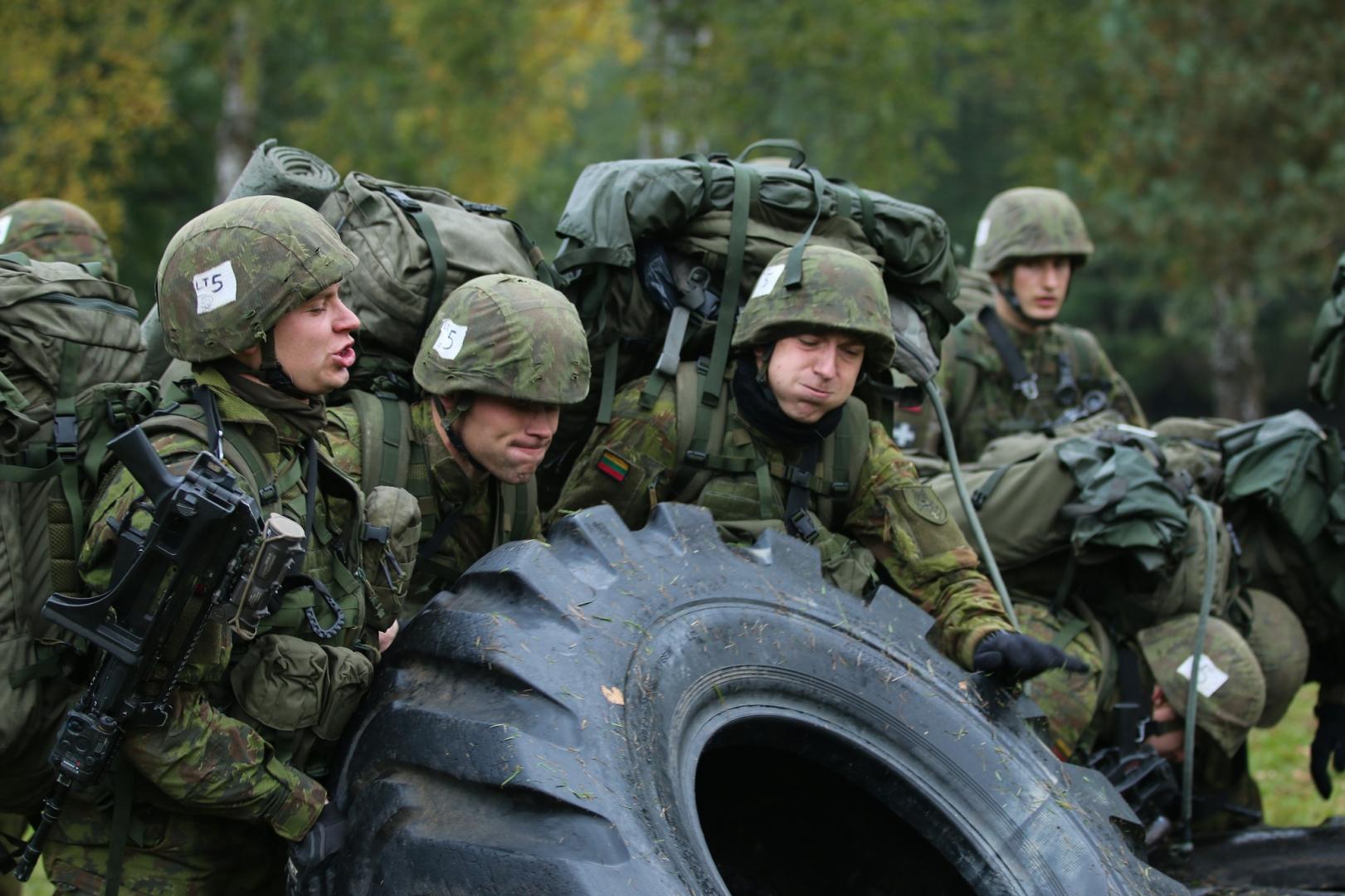 Литовские солдаты переворачивают шину в ходе учений в Баварии (Германия), 20 октября 2015 года
