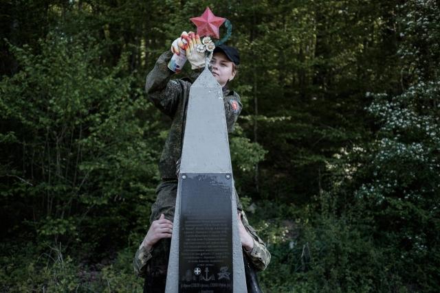 Убираются на памятнике двум неизвестным солдатам. Судя по всему, они раненные пытались выбраться к своим, но не смогли и погибли. В 1960 году их останки случайно обнаружили под большим камнем