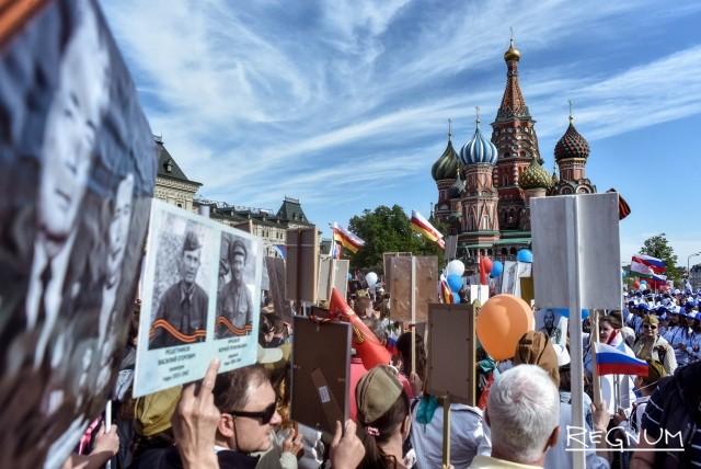 Поток людей движется в колонне «Бессмертного полка» от Красной площади