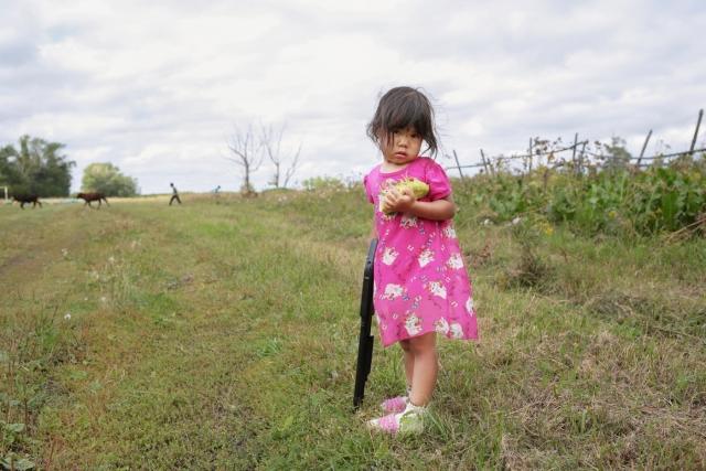 Девочка в повседневной одежде неподалеку от дома. Деревня Селивановка, Омская область