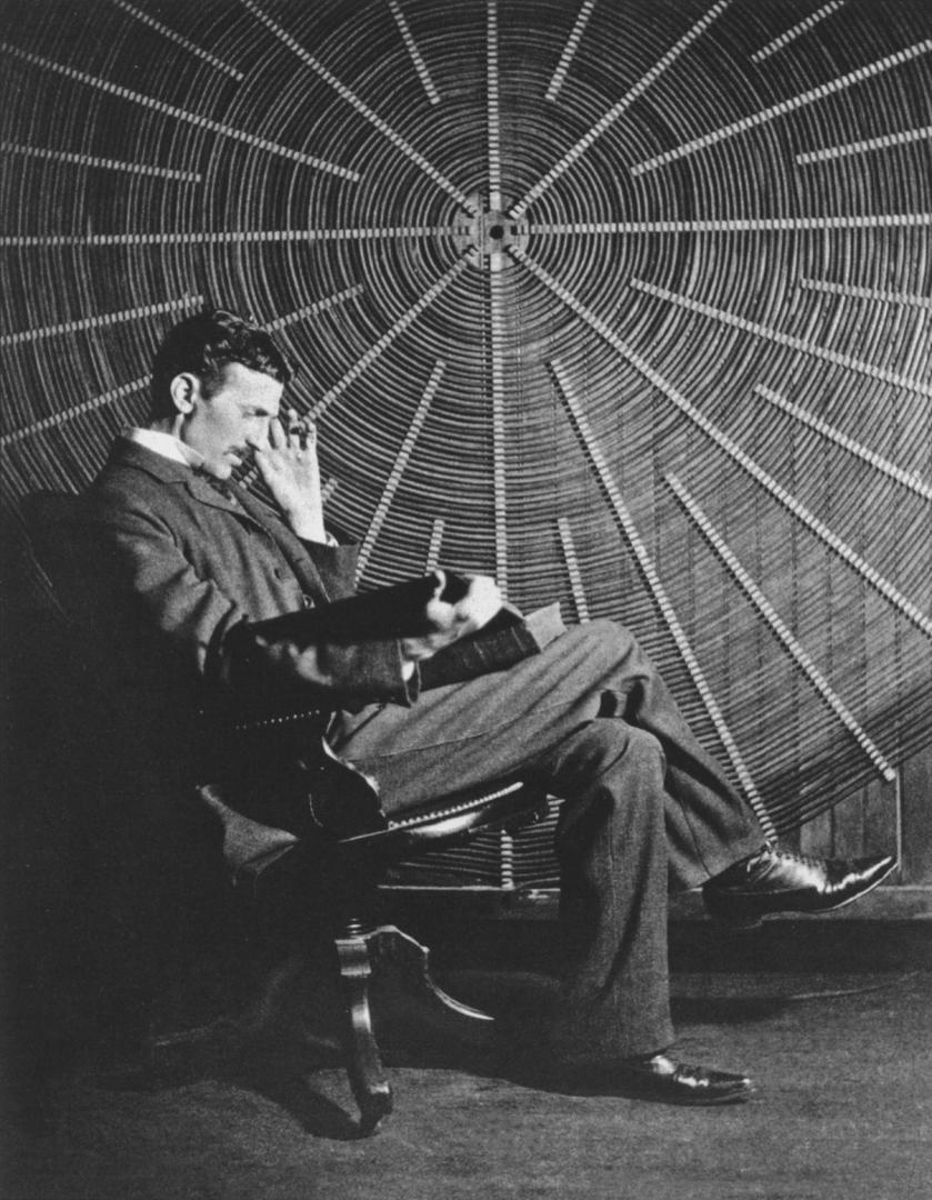 Тесла с «Теорией натуральной философии…» Руджера Бошковича на фоне катушки ВЧ трансформатора в своей лаборатории на Хаустон-стрит