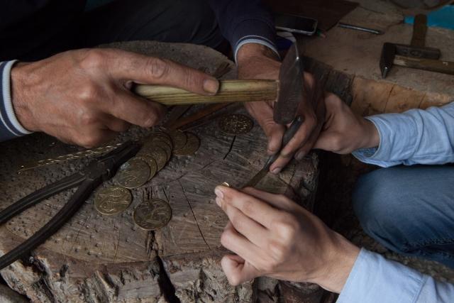 Вахид делает узор на браслете, который вырезан из старого медного самовара