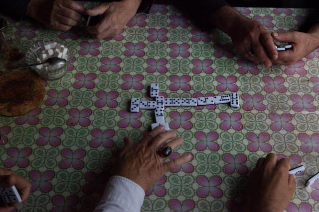 Мужчины играют в домино в кафе