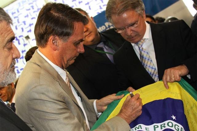 Жаир Болсонару расписывается на флаге