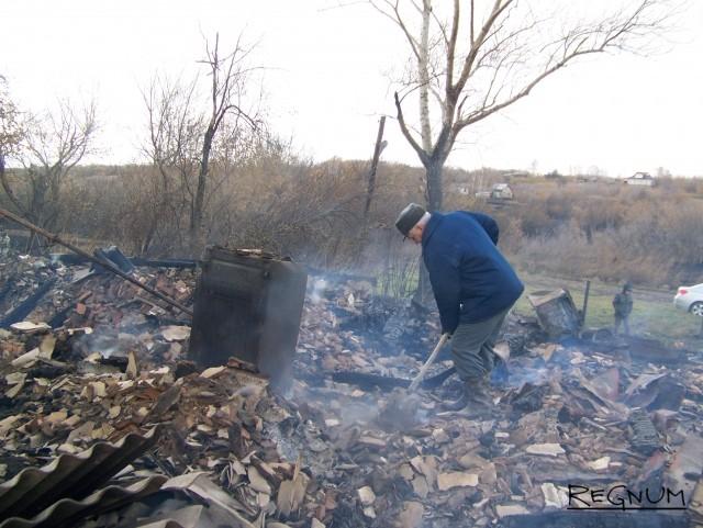 Житель Володарки Юрий, который работает вместо спасателей на пожарище, где то и дело возникают языки пламени. В условиях штормового ветра огонь запросто может дойти до дома Юрия