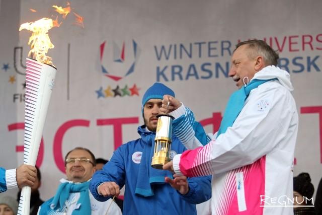 Александр Беглов зажигает факел от колбы с огнем