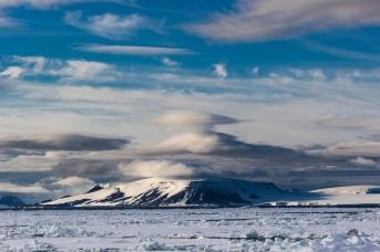 Типичный арктический пейзаж – скалистый остров, ледник, лентикулярные облака
