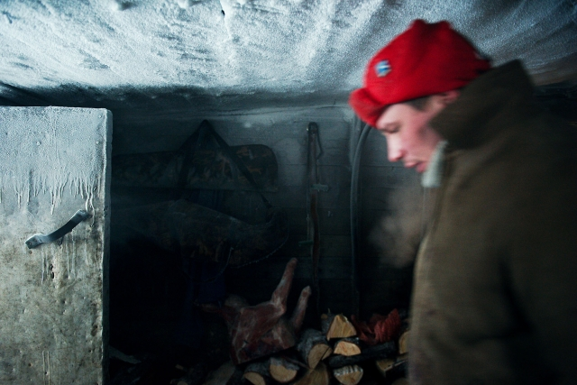 Алексей, охотник из бригады Николая Николаевича, проходит через холодную хозяйственную пристройку дома. Промысловые избушки находиться в 500–800 км севернее полярного круга. Суровые морозы могут достигать – 60 °С