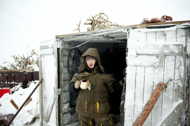Молодой охотник из бригады Николая Николаевича пьет чай у входа в дом