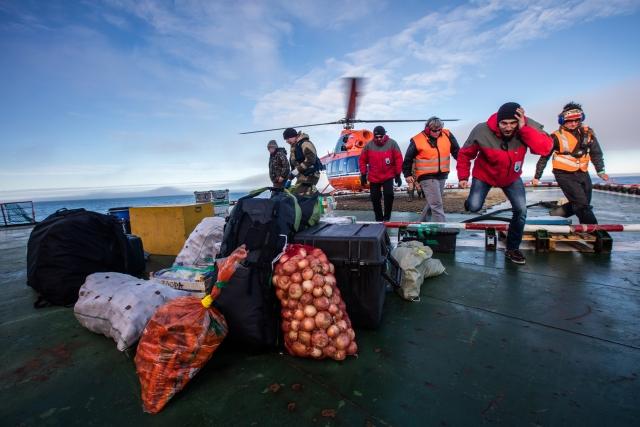 Идёт погрузка продуктов и вещей на вертолёт, который высаживает ученых на остров Нортбрук