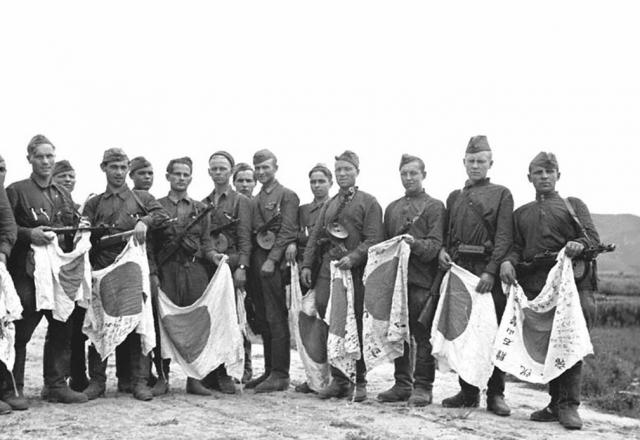 Советские солдаты с трофейными японскими флагами. 1945