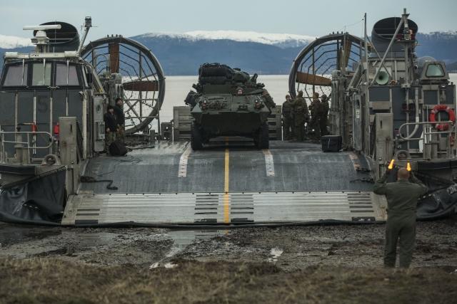 Морские пехотинцы и моряки США выгружают легкий бронированный автомобиль с десантного корабля на воздушной подушке. Пляж Алвунд, Норвегия. Учения Trident Juncture