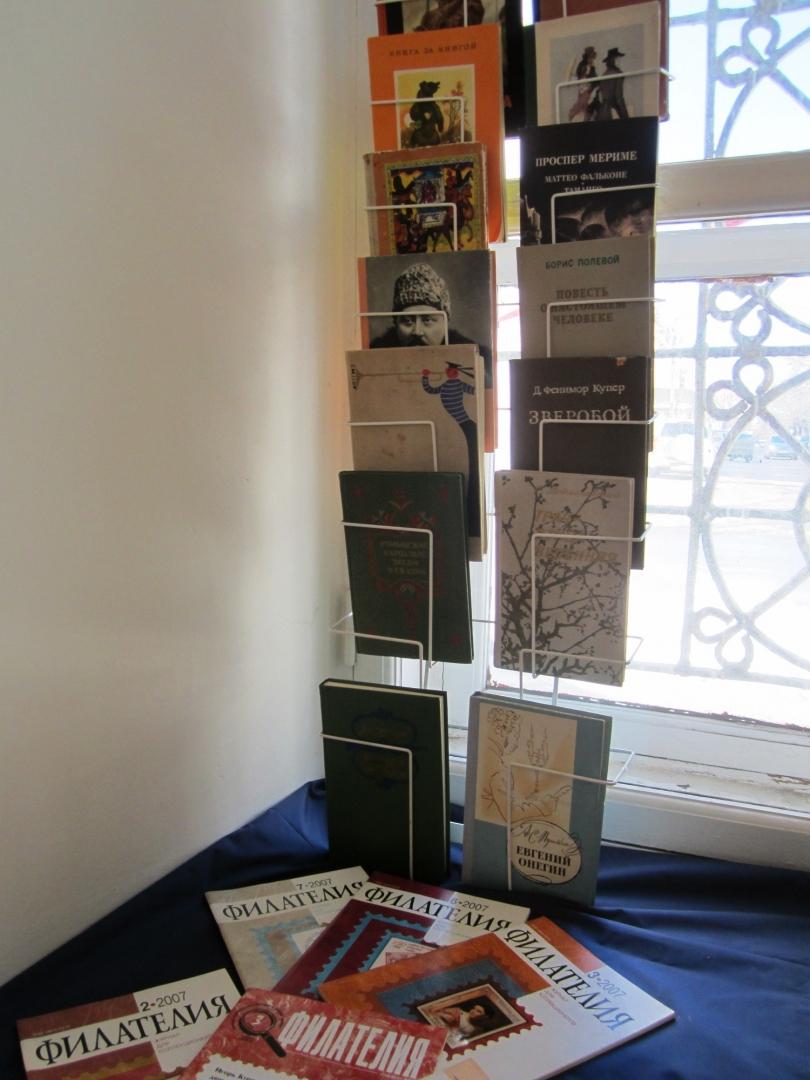На полке для буккроссинга размещены книги и  журналы.