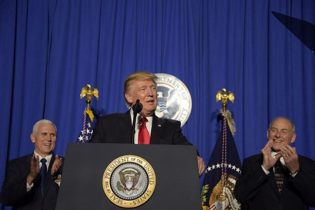 Президент Дональд Трамп выступает с речью перед сотрудниками Департамента национальной безопасности в Вашингтоне. 2017 года. На заднем плане Майкл Пенс (слева) и Джон Келли (справа)