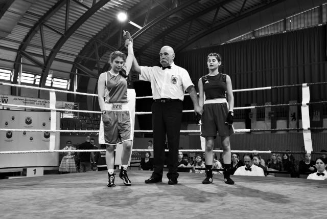Судья поднимает вверх руку чемпионки