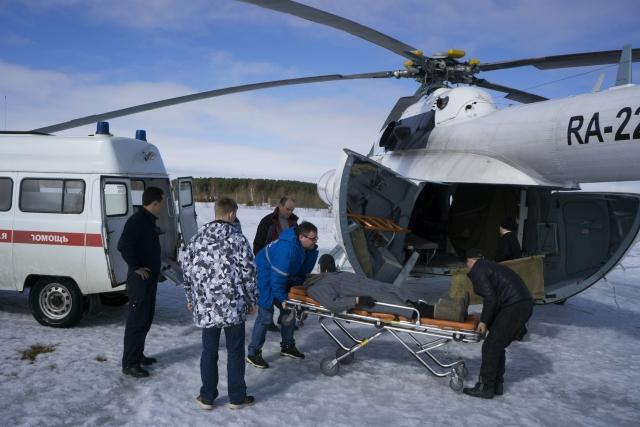 Пожилую пациентку перемещают из вертолета в карету скорой помощи