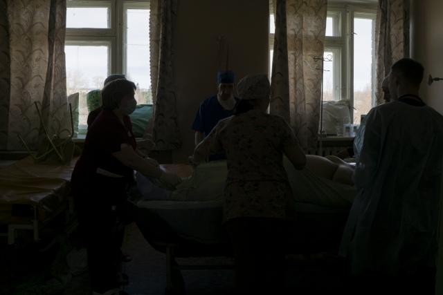 Врачи и медсестры больницы, расположенной в одном из небольших областных населенных пунктов, готовят к перелету женщину с тяжелой формой воспаления легких