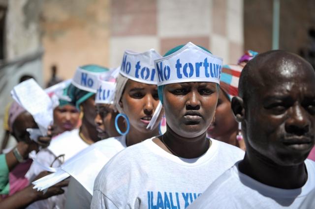 Люди в шляпах с надписю «Без пыток», выстраиваются в очередь перед выступлением на мероприятии, посвященном Дню прав человека, возле Центральной тюрьмы Могадишо в Сомали