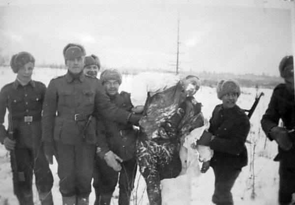 Финские военнослужащие позируют рядом с телом замерзшего красноармейца. 1939