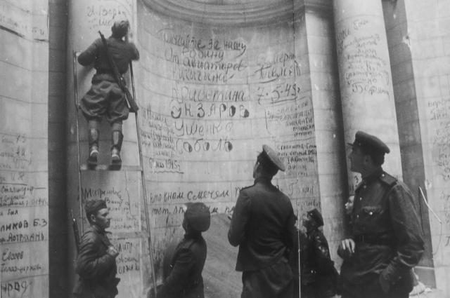 Советские бойцы и командиры оставляют победные надписи и свои фамилии на стенах Рейхстага. Май 1945 года