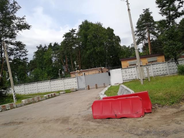 Вид бывшей проходной КУОС (справа за воротами). За зданием, которое слева за воротами, до продажи территории располагалась Аллея славы и памятник сотрудникам ГСН «Вымпел»