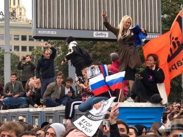 Танец девушки на кабинке туалета под песню Face на митинге в Москве 10 августа