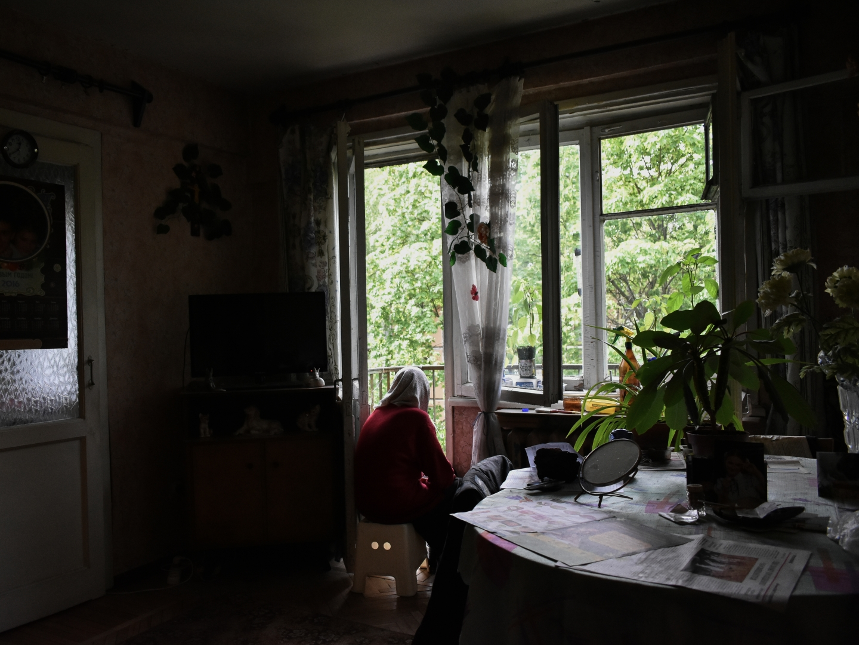 Бабушка «гуляет», сидя на пороге балкона