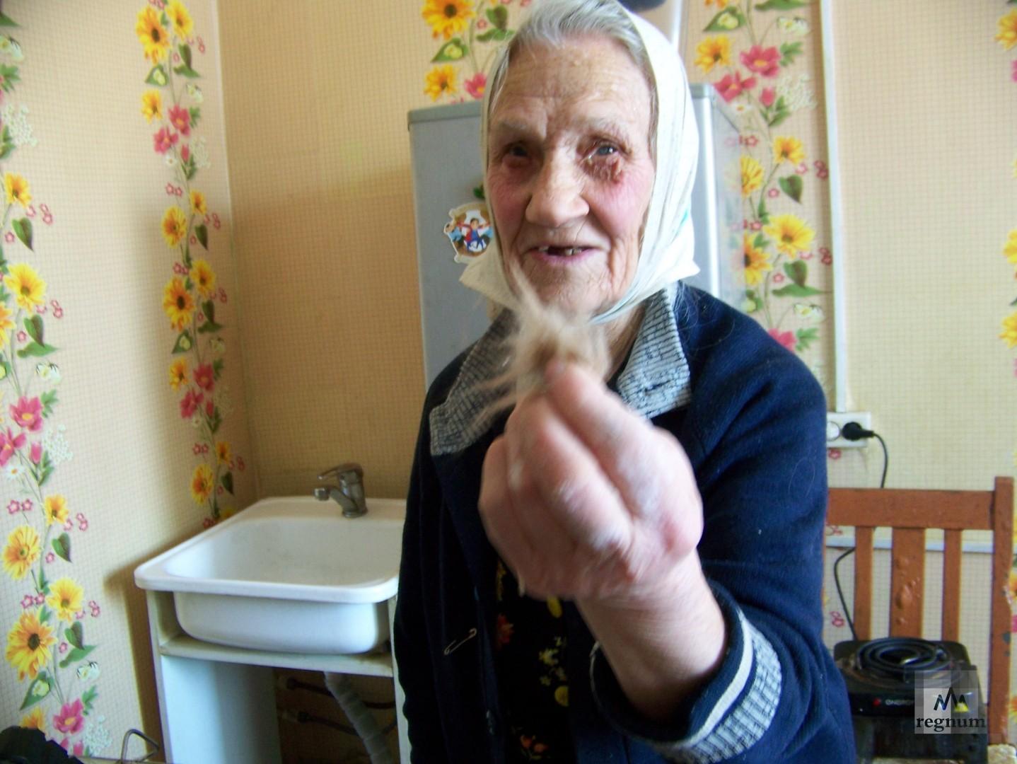 Бабушка Тамара показывает стекловату, которой заполнены стены