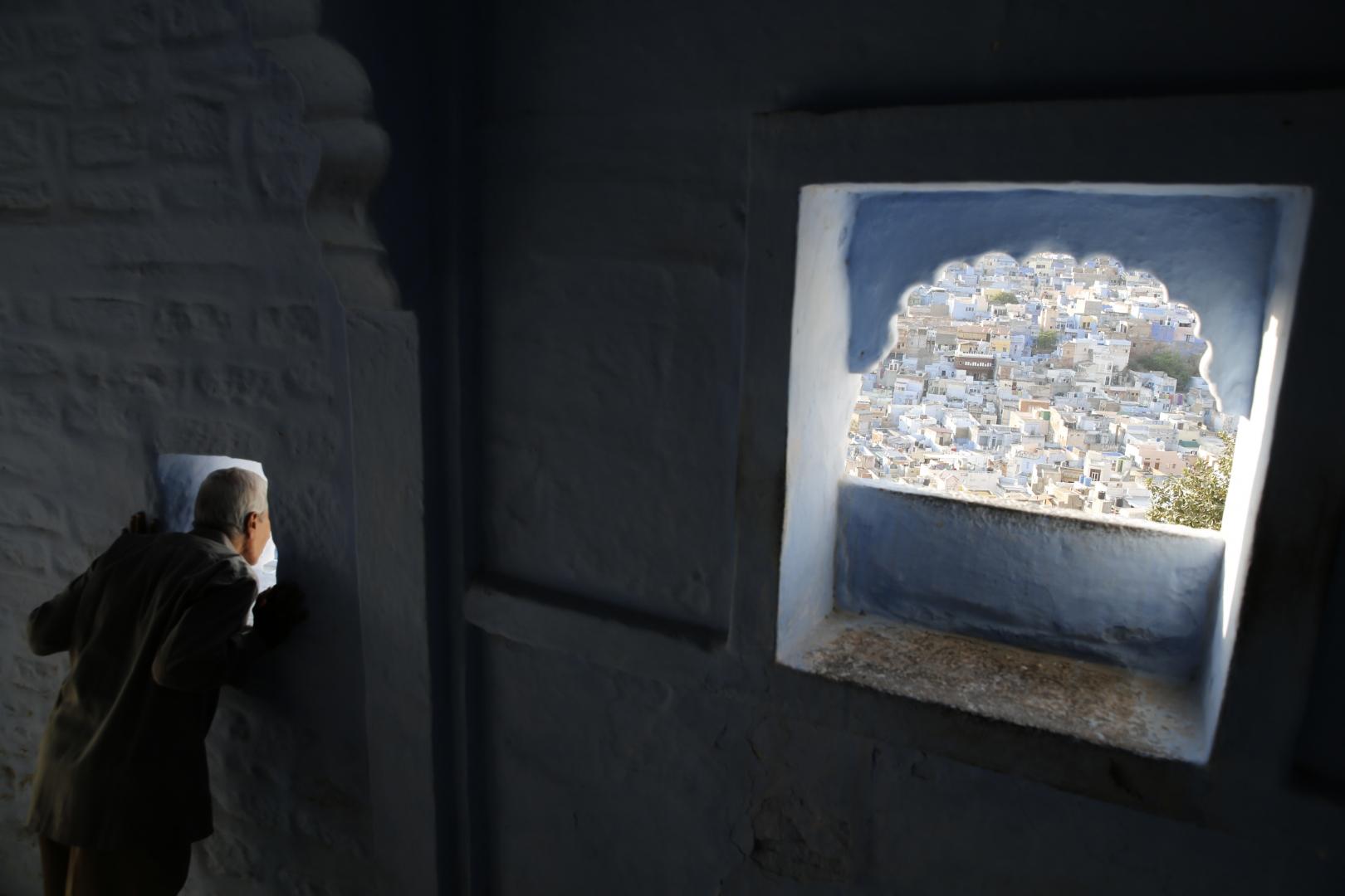 Мужчина смотрит на город через стену в крепости Мерангар. Это самая высокая точка города, расположенная на высоте 125 метров